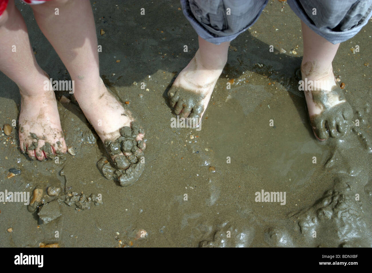 Children's feet covered in mud and sand on Charmouth beach, Dorset - Stock Image