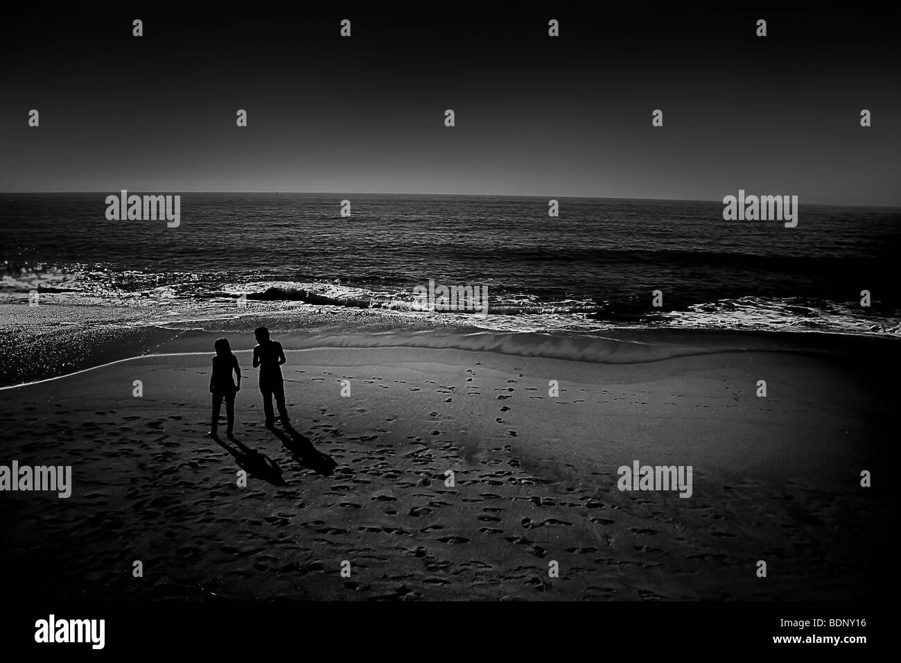 A couple silhouetted on a beach - Stock Image