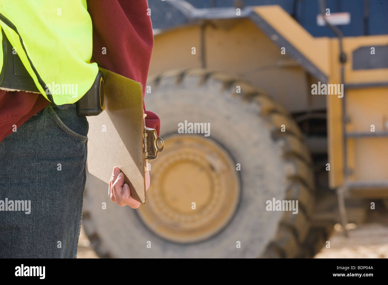 Engineer holding a clipboard at a construction site - Stock Image