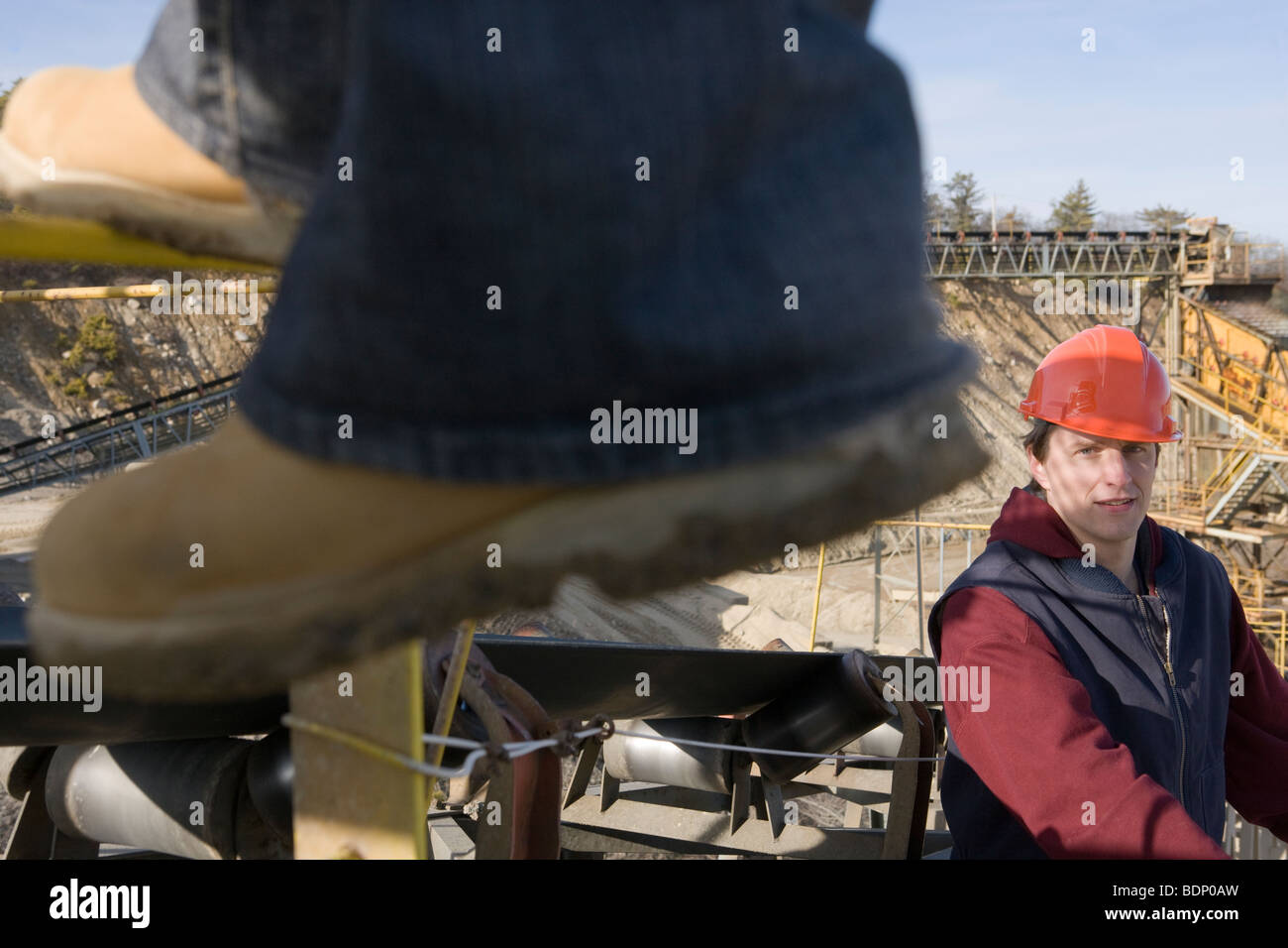 Two engineers on a conveyor belt at a construction site - Stock Image