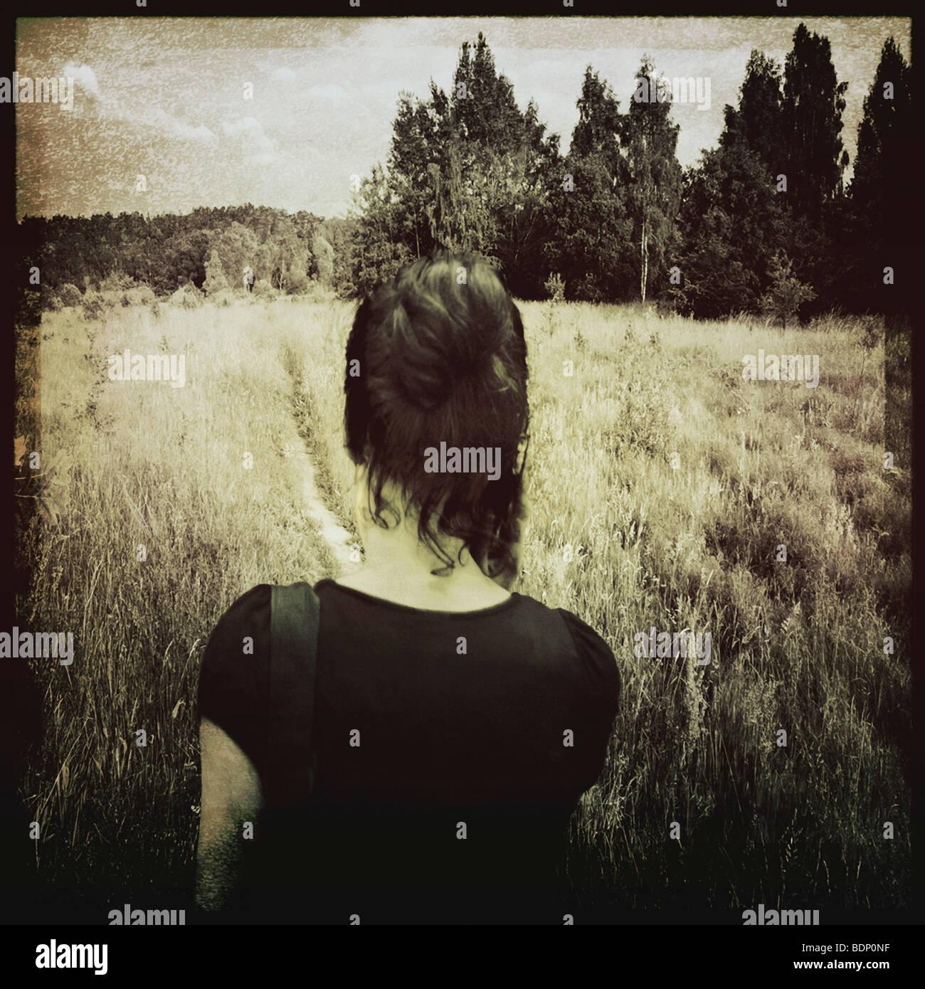A woman walking across a field. - Stock Image