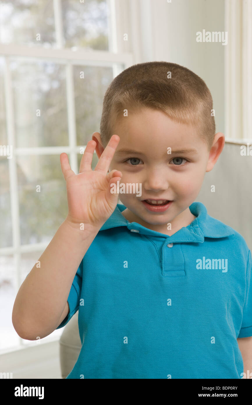 Boy signing the letter 'F' in American Sign Language - Stock Image