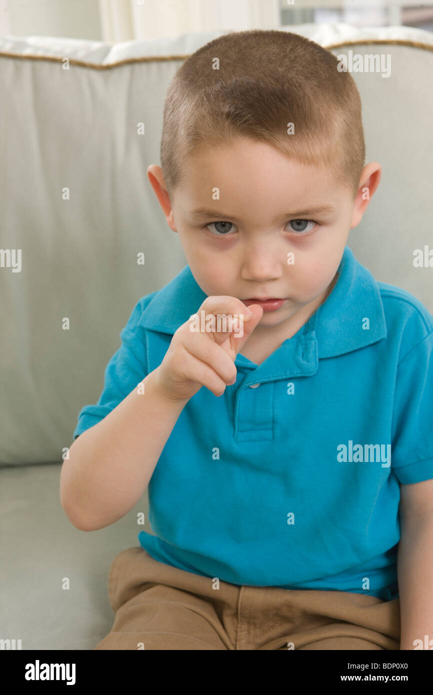 Boy signing the letter 'R' in American Sign Language - Stock Image