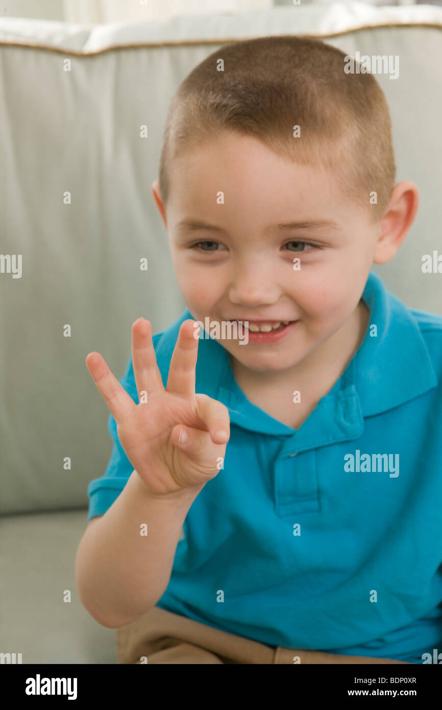 Boy signing the number '9' in American Sign Language - Stock Image