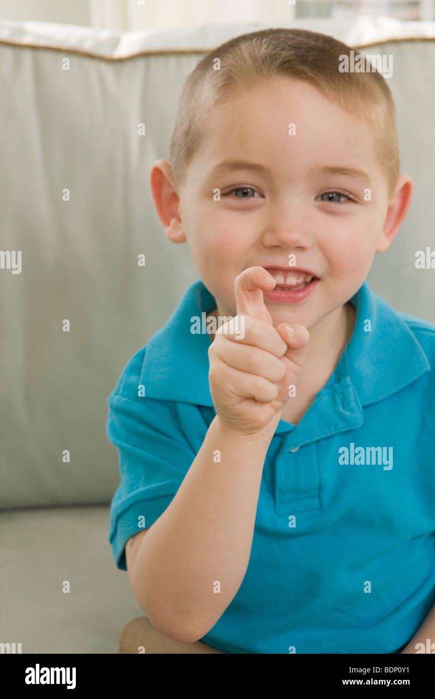 Boy signing the letter 'X' in American Sign Language - Stock Image