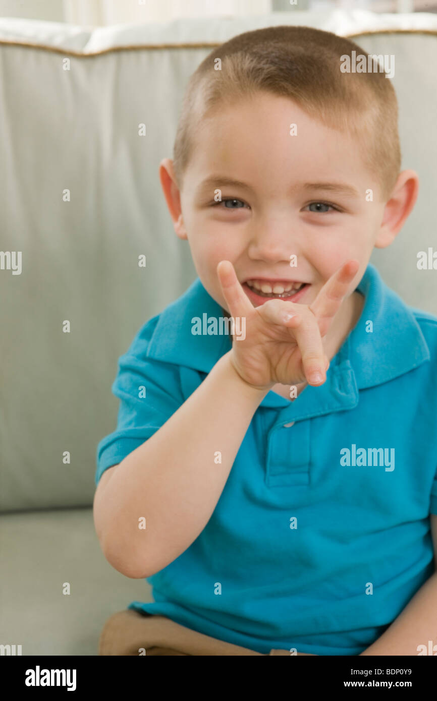 Boy signing the number '8' in American Sign Language - Stock Image