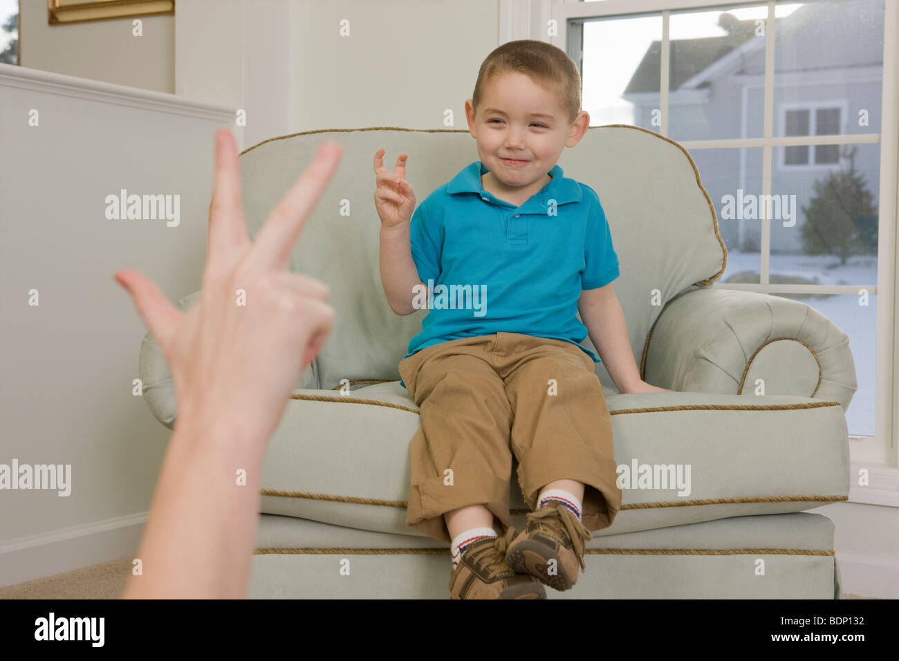 Boy signing the number '3' in American Sign Language - Stock Image