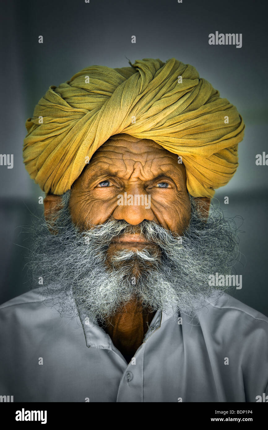 India, Rajasthan, Jodhpur, older Rajasthani Indian man with bushy gray beard wearing yellow turban - Stock Image