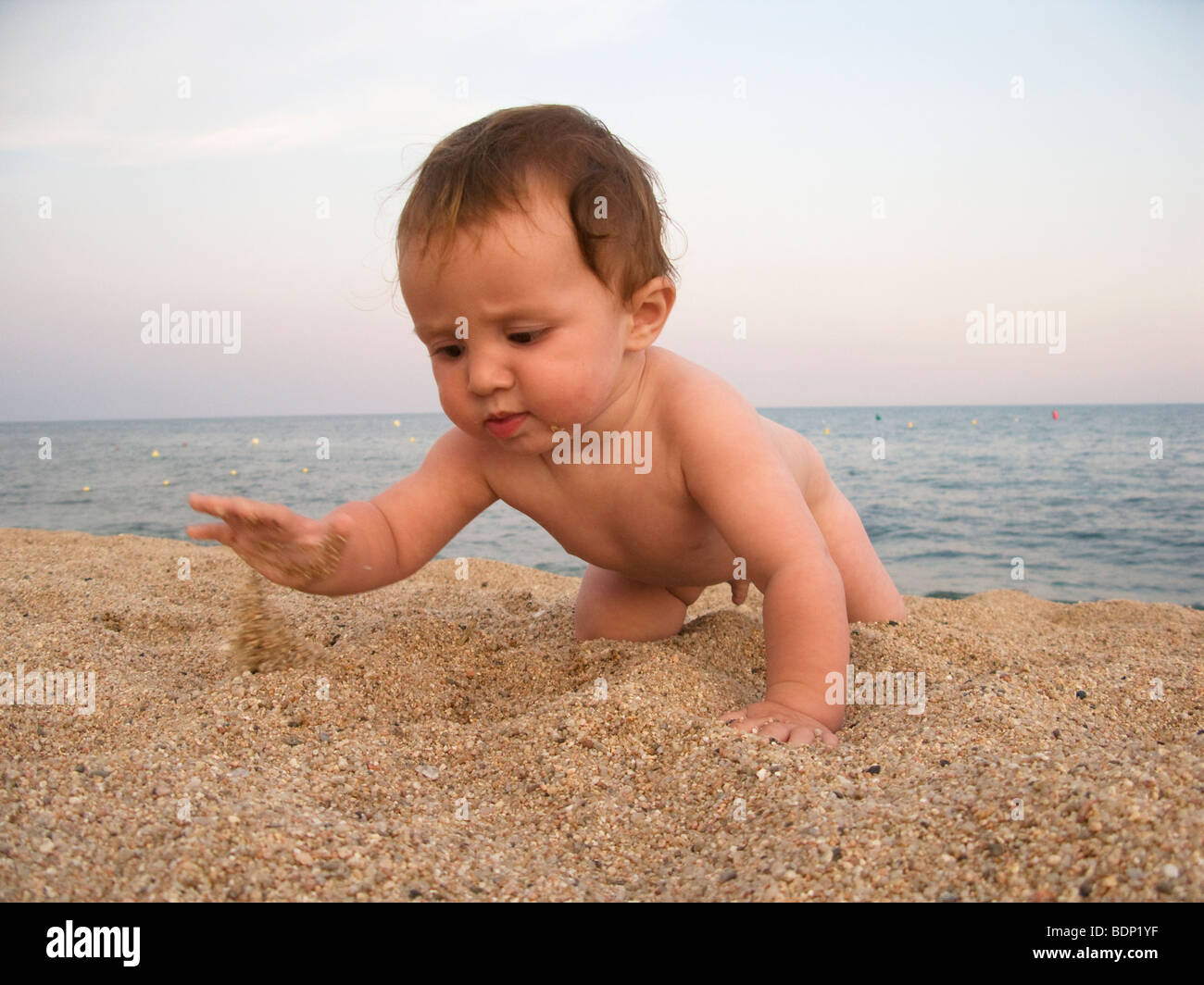 bay boy playing with the sand on the beach - Stock Image
