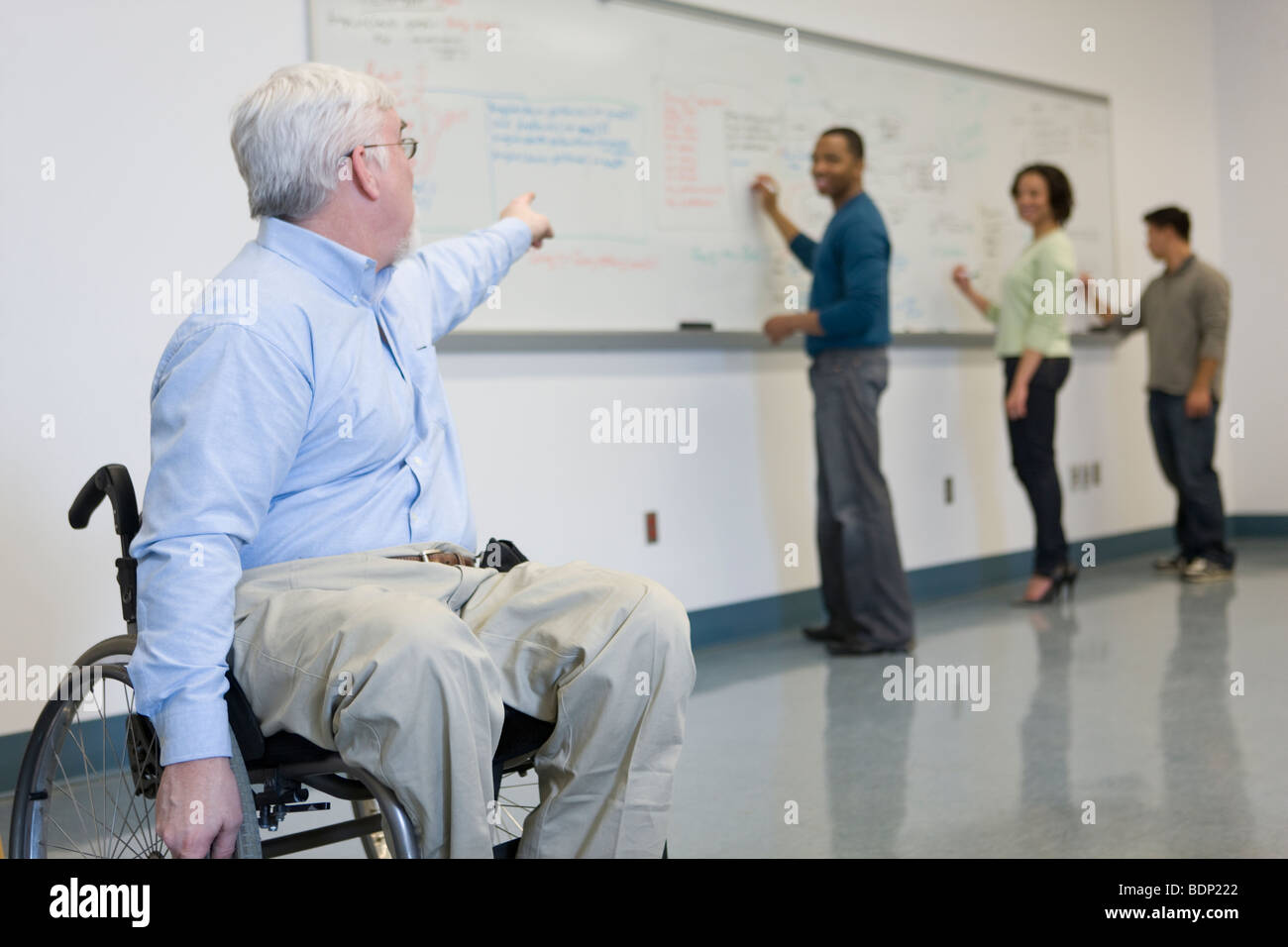 University professor in a wheelchair pointing at his students writing on a whiteboard - Stock Image