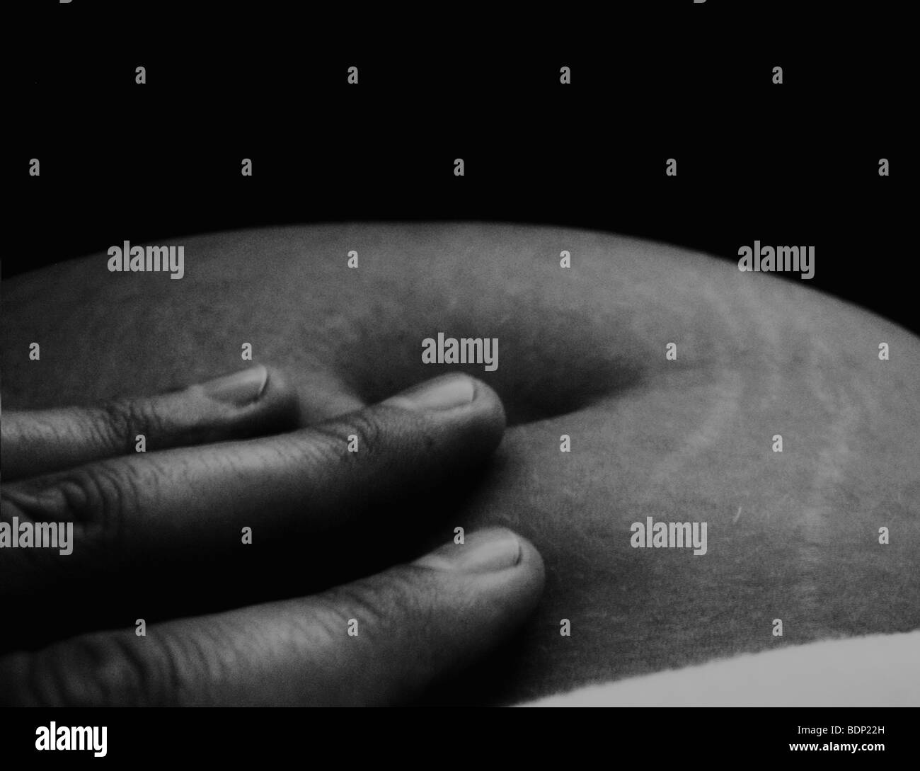 Close up of a woman's body with fingers touching skin - Stock Image