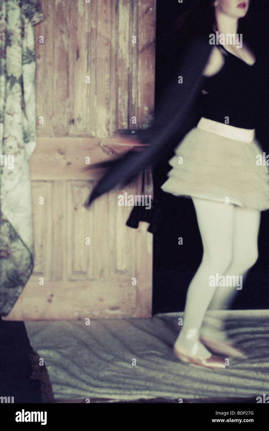 A young woman wearing a white short skirt and black jacket spinning around - Stock Image