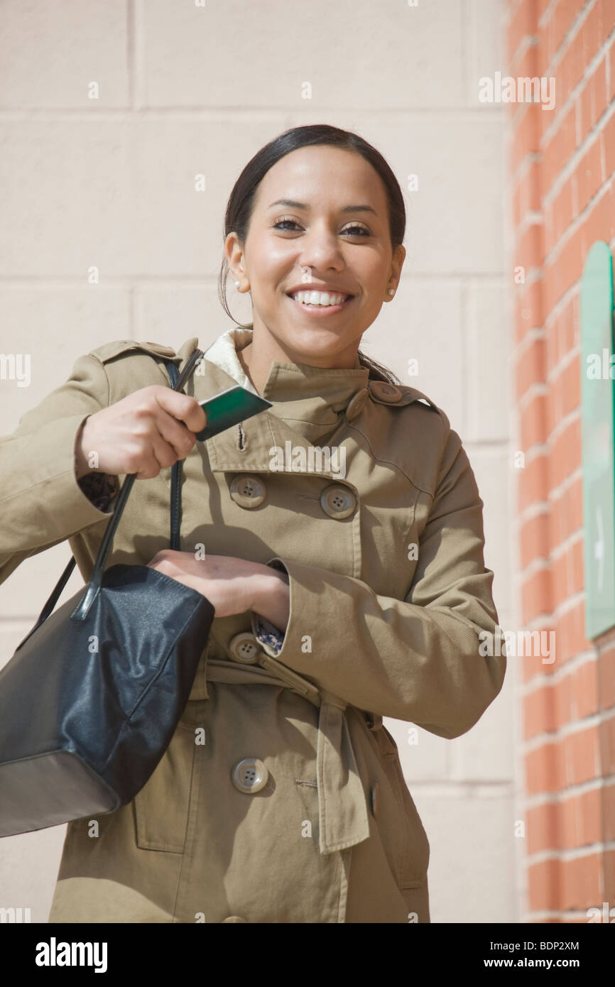 Hispanic woman standing in front of a bank access slot - Stock Image