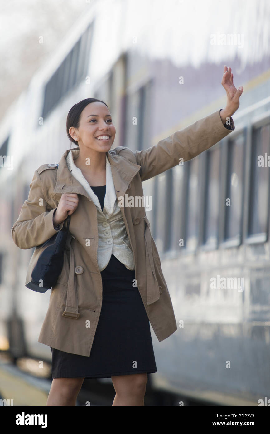 Hispanic woman waving goodbye at a railroad station platform - Stock Image