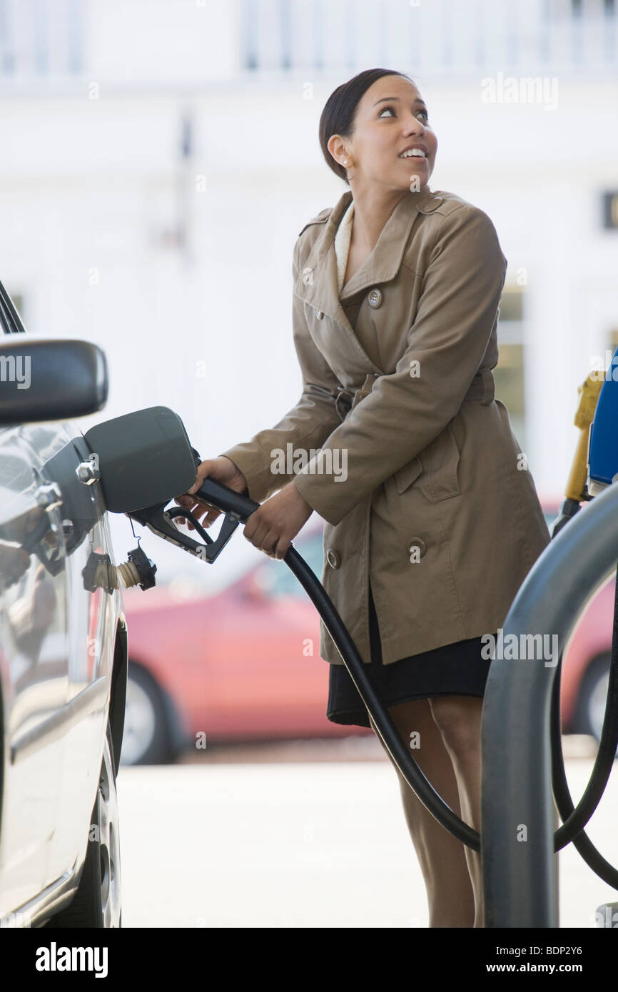 Hispanic woman filling a car at a gas station - Stock Image
