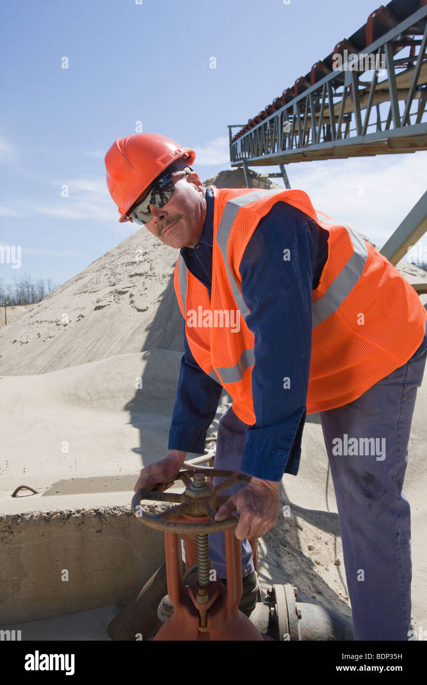 Engineer turning valve at a plant - Stock Image