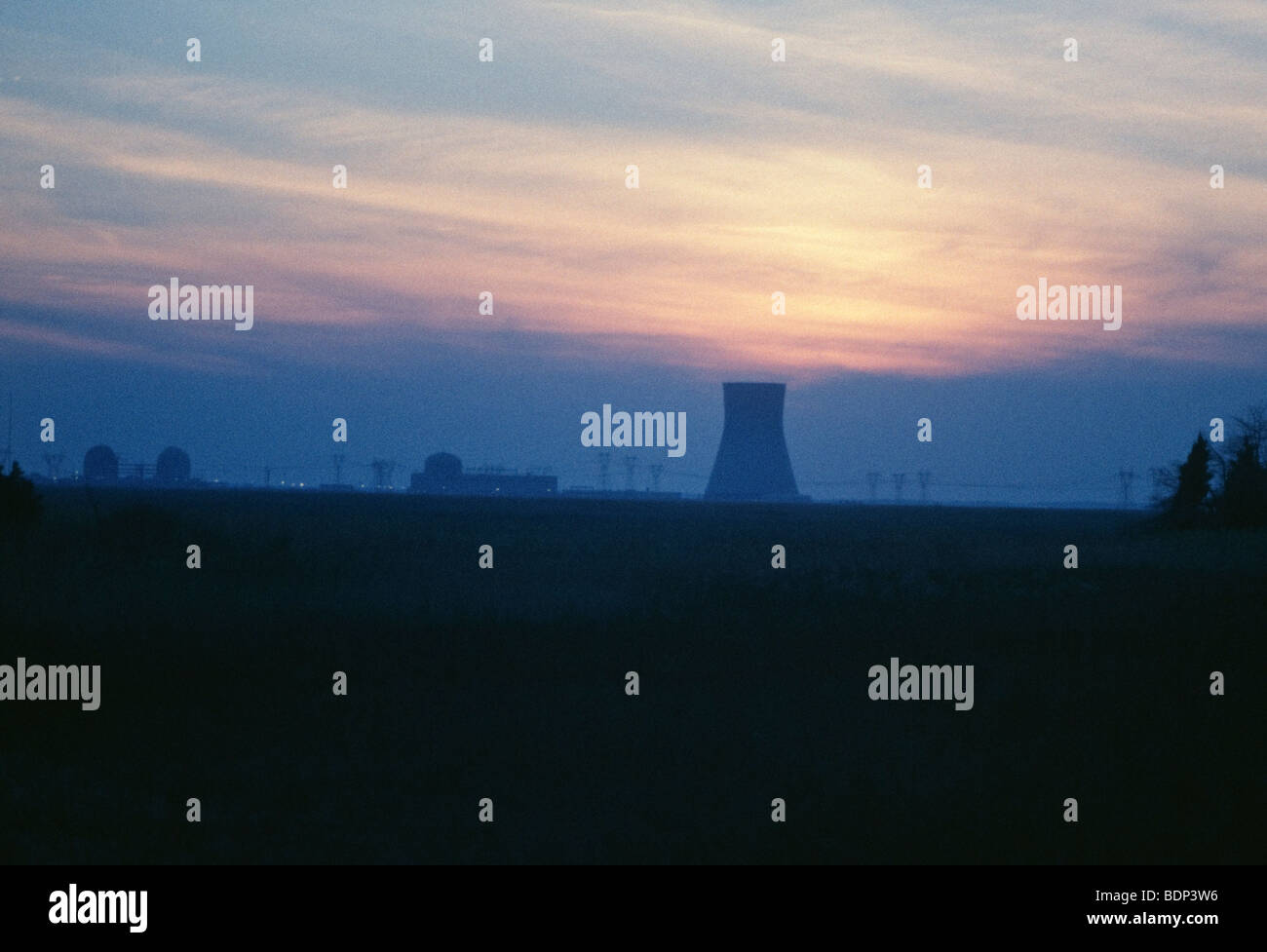 Nuclear cooling tower outside of Philadelphia, PA in sunset. Transmission wired in foreground - Stock Image