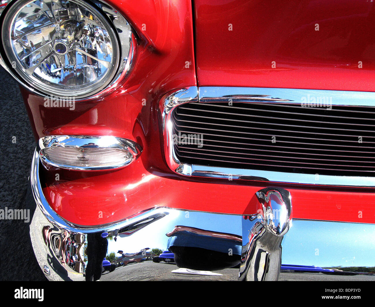 The front of a red car with shiny chrome bumper and grill - Stock Image