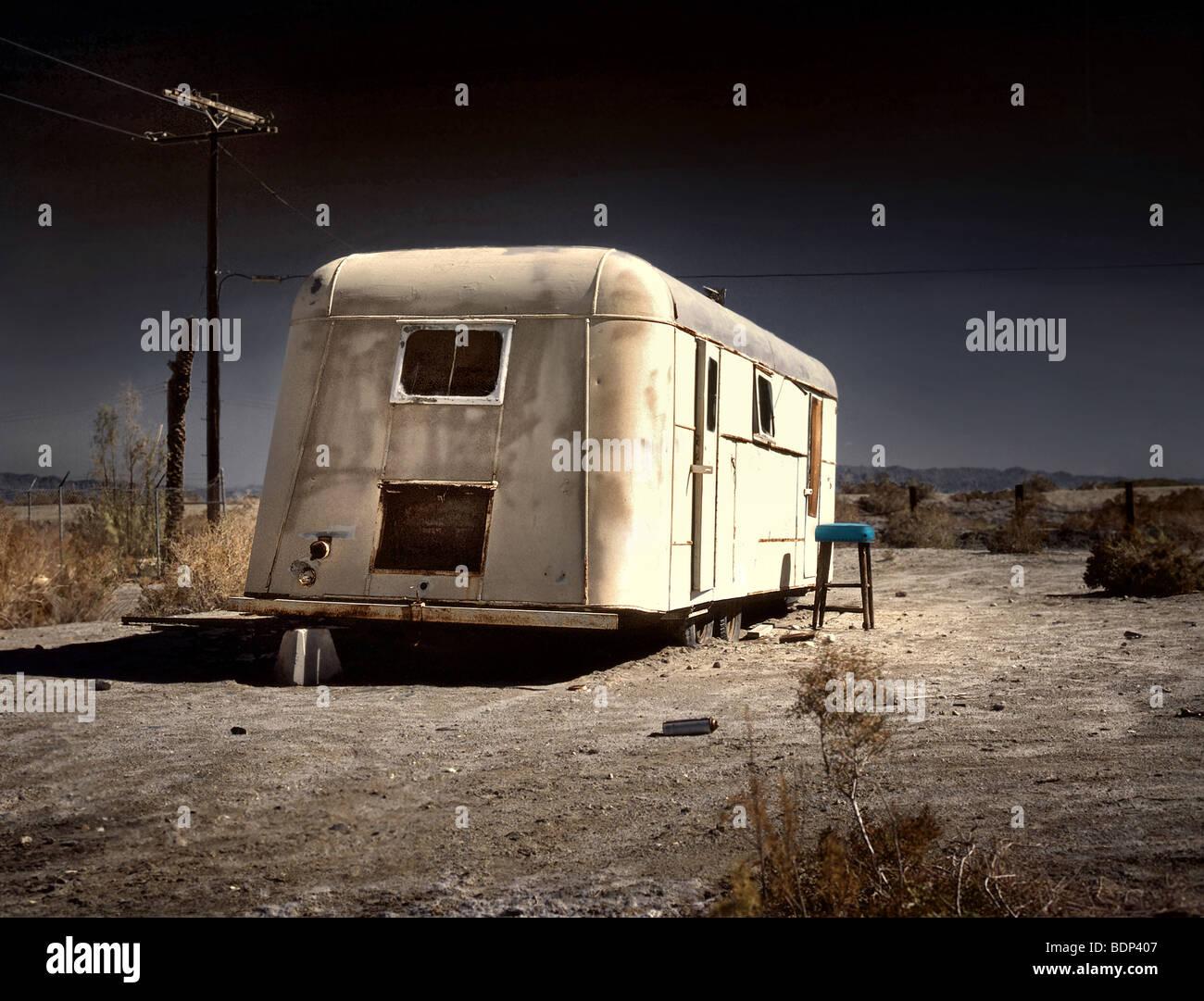 An old white caravan left to rot in the desert - Stock Image