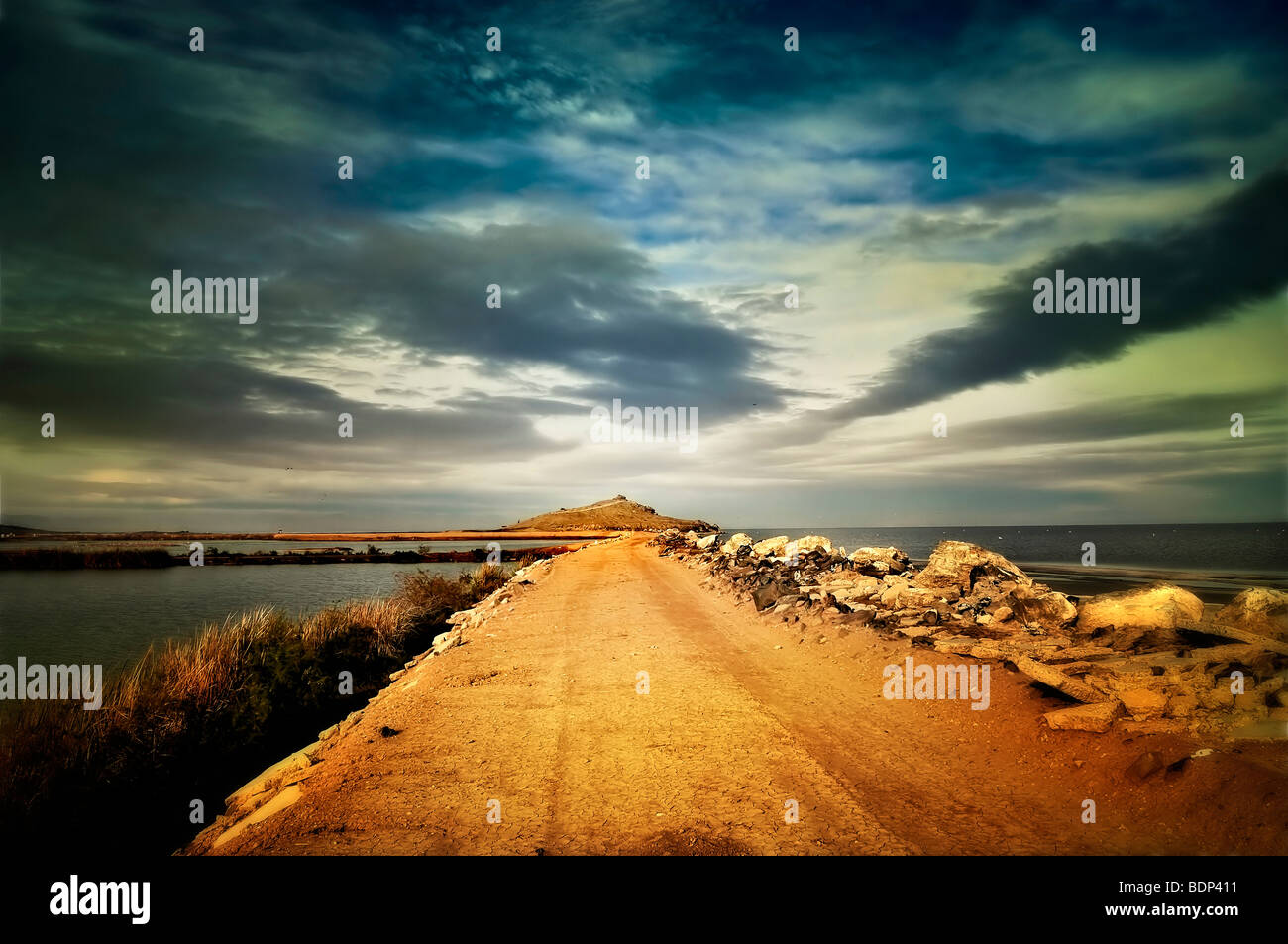 A road surrounded by water leading into the distance beneath a cloudy sky - Stock Image