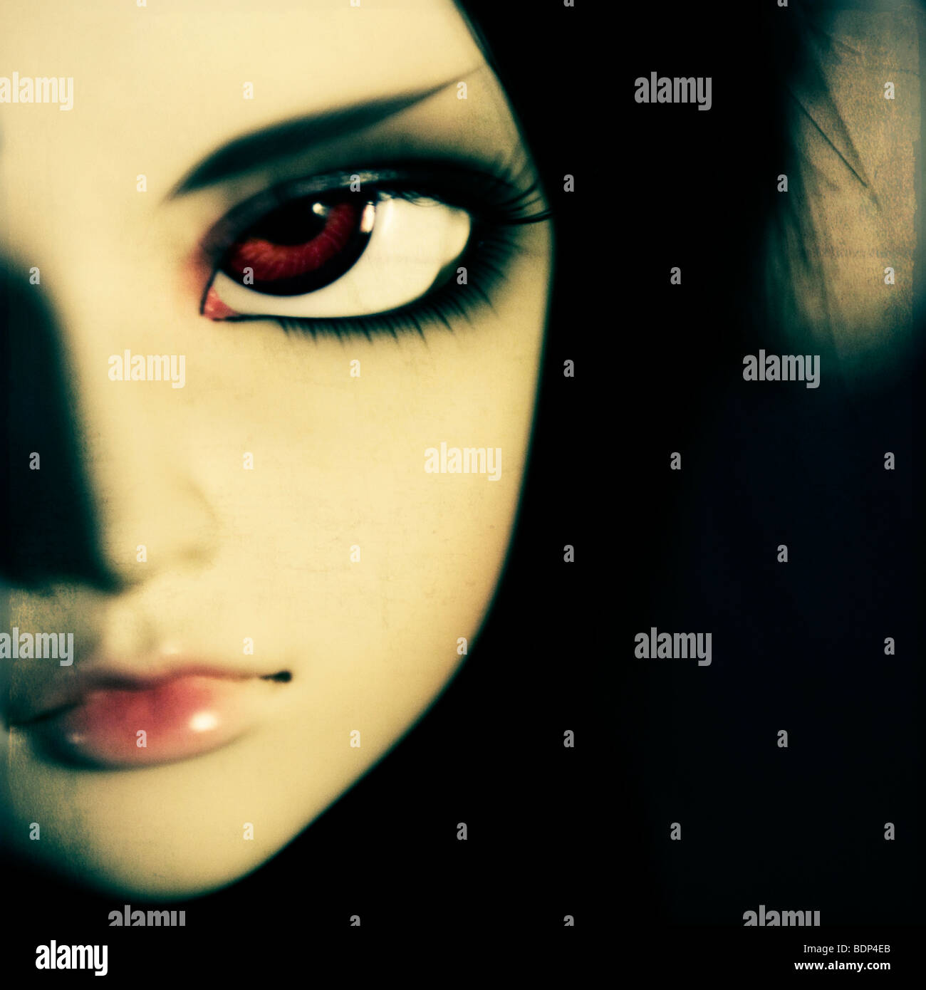 Close up of a sultry dolls face with large brown eyes - Stock Image