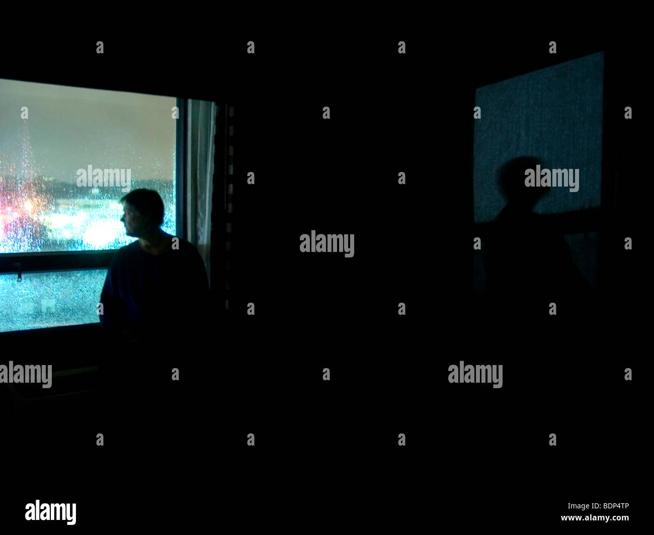 A figure standing in a dark room looking our of a window - Stock Image