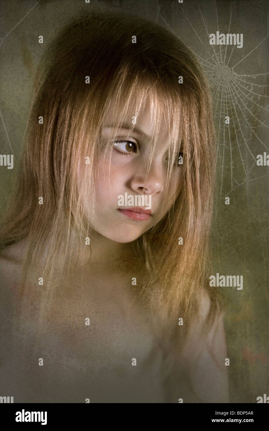 young child looking serious with cobwebs in the background - Stock Image