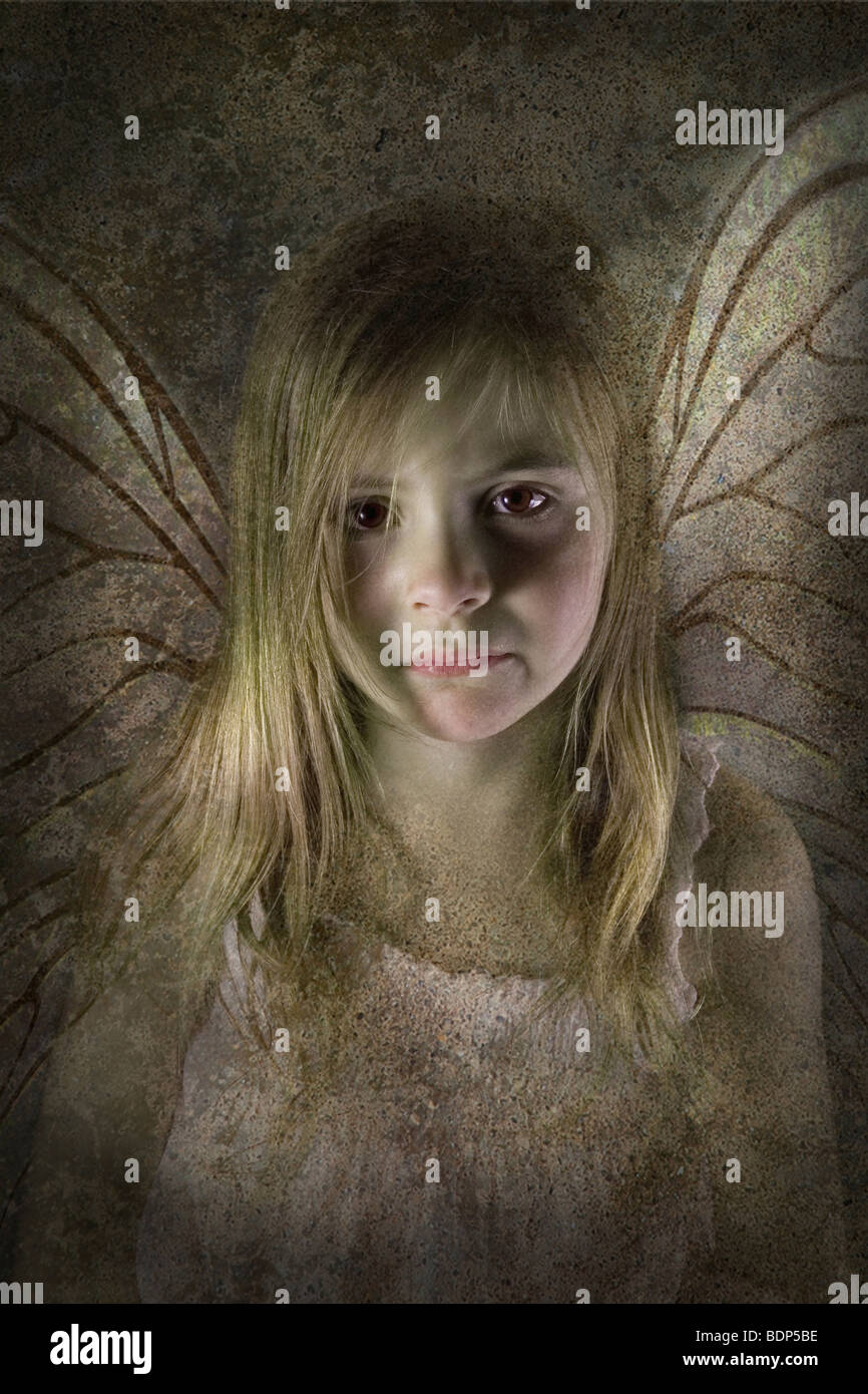 Young fairy child with wings looking sad and desolate directly at the camera - Stock Image