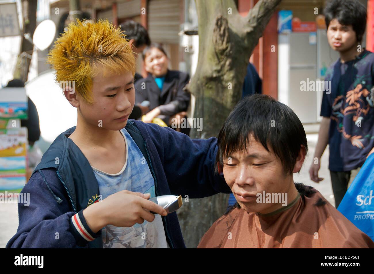 Man receiving haircut in street salon Hunan Province China - Stock Image