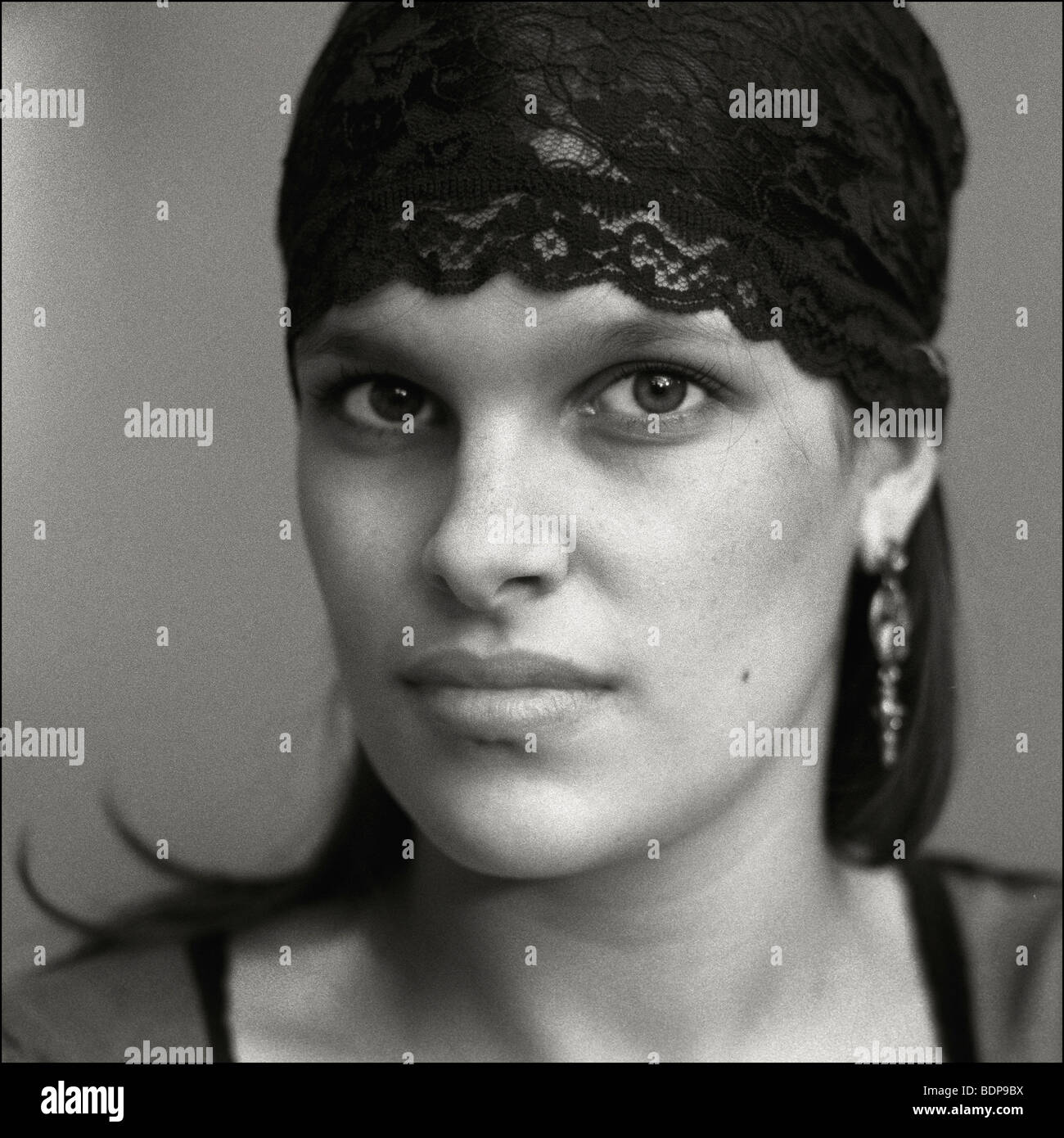 A woman with strong features wearing a black lace headband - Stock Image