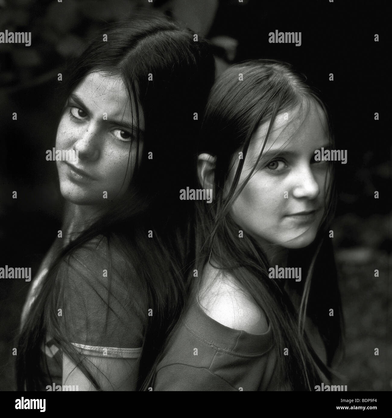 Two young women standing back to back Stock Photo