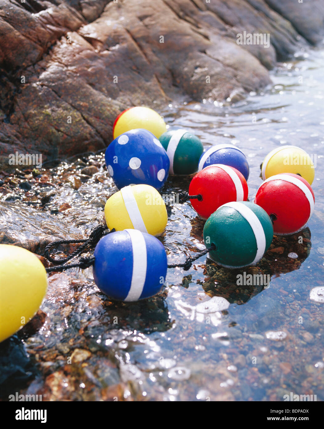 Brightly coloured floats at the water''s edge, Sweden. Stock Photo