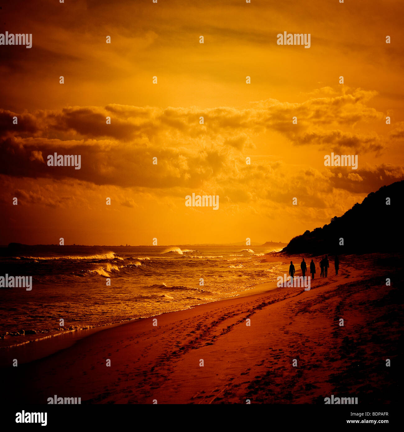 An Australian sunset with figures walking in the distance - Stock Image