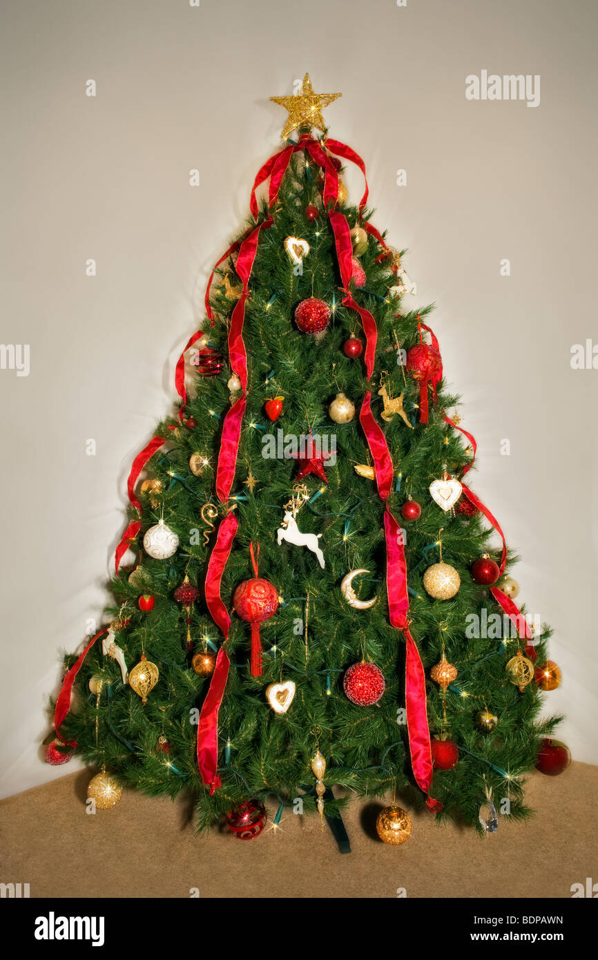 Traditional decorated Christmas tree in red and gold theme - Stock Image