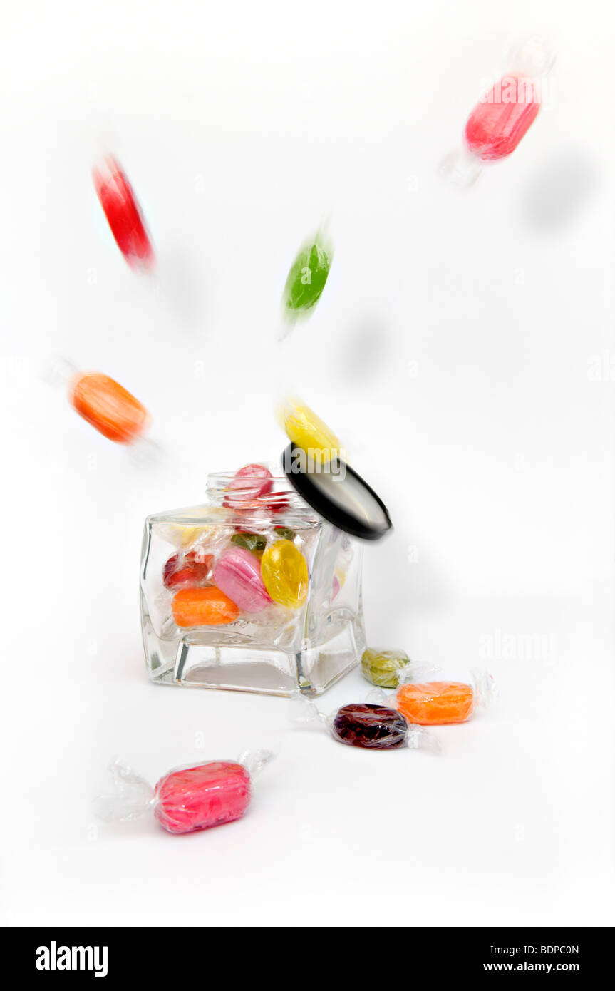 Studio shot of coloured boiled fruity sweets exploding from glass jar against a white background with lid falling - Stock Image