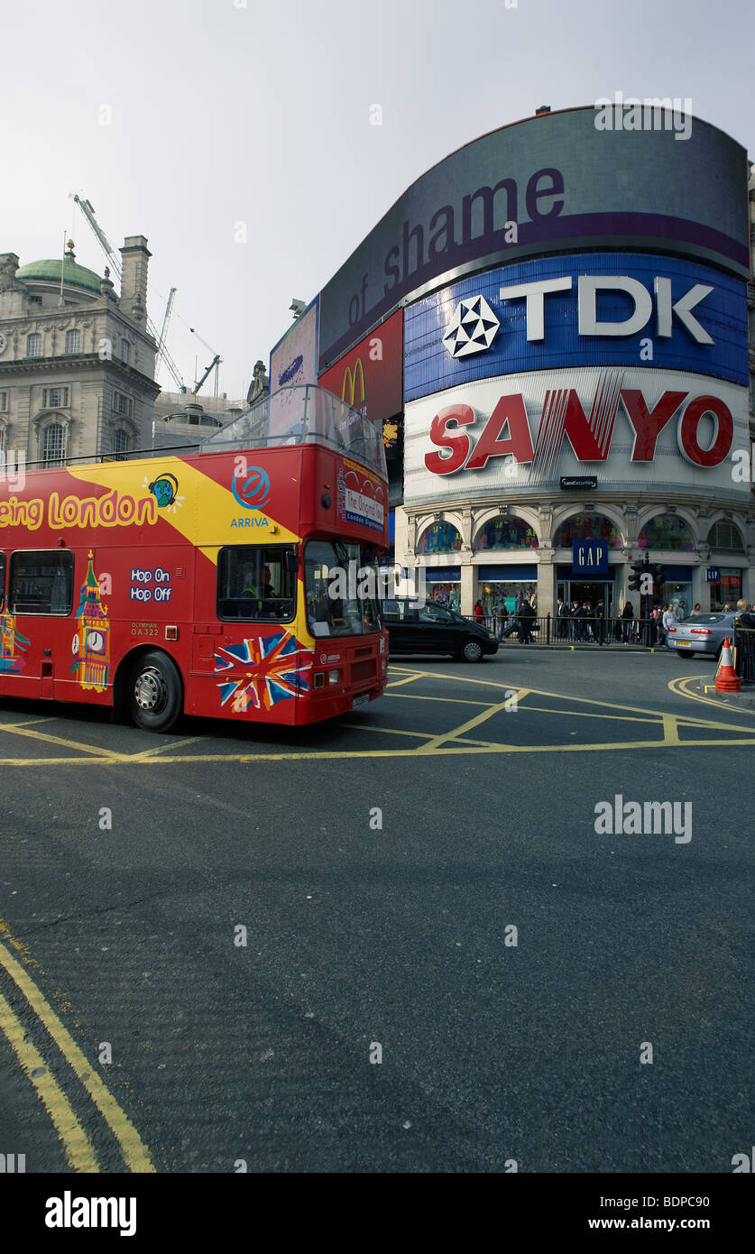 A london red sightseeing bus drives around Picadilly Circus. - Stock Image