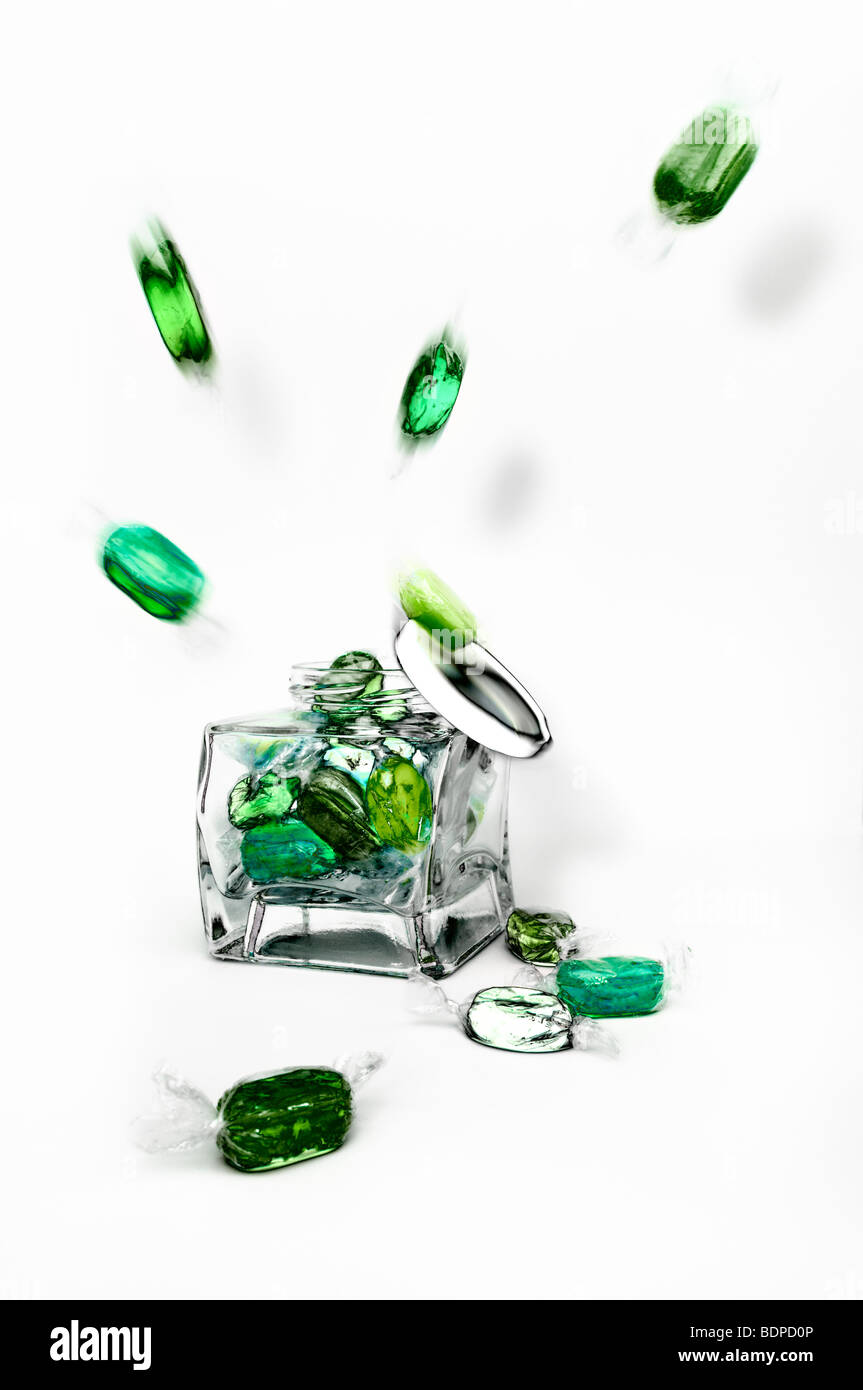 Studio shot of green boiled fruity sweets exploding from glass jar against a white background with lid falling off - Stock Image