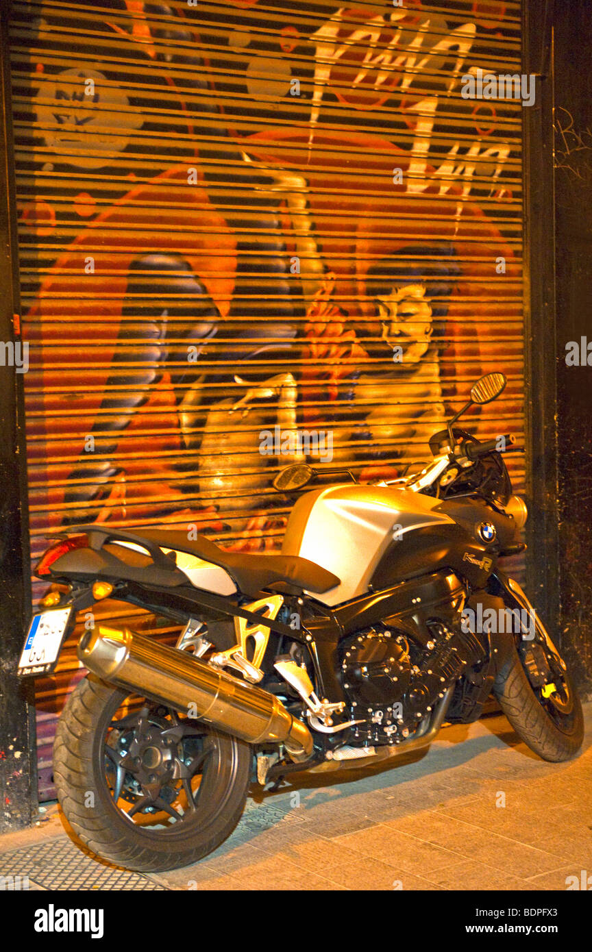 A motorbike parked by a shop in Spain - Stock Image