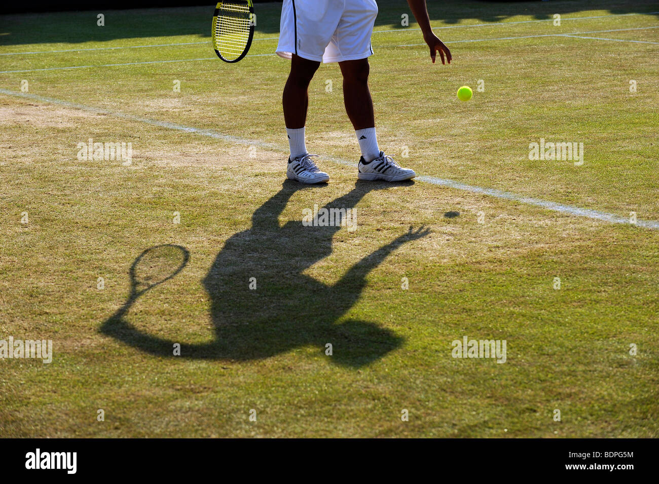 A player and shadow as he bounces the ball before serving during the 2009 Wimbledon Tennis Championships - Stock Image