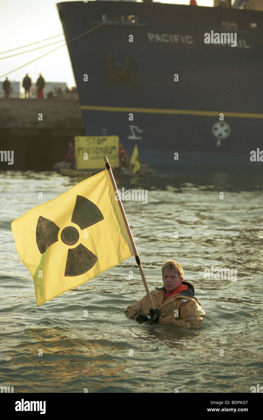 GP activist in the water holding a flag bearing the radiation symbol with the GP inflatable with the 'Stop Plutonium' - Stock Image