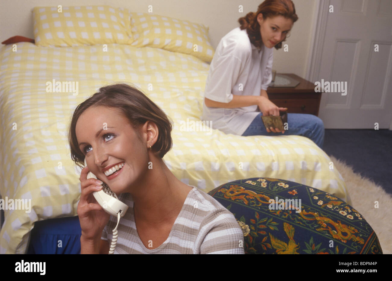 woman taking money from a friend's purse while her friend is on the phone - Stock Image