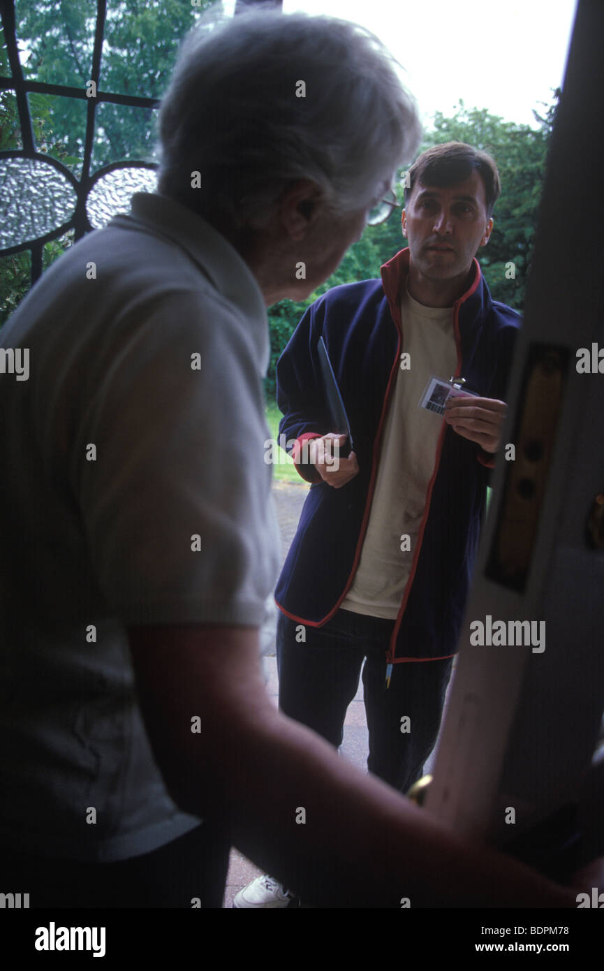 elderly woman opening the door to a workman or salesman - Stock Image