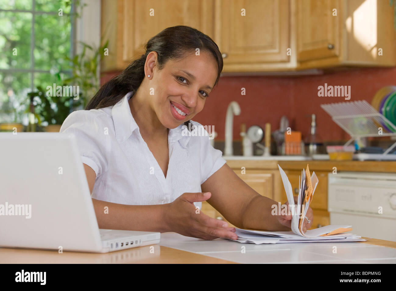 Hispanic woman sitting in front of a laptop and holding bills in the kitchen - Stock Image