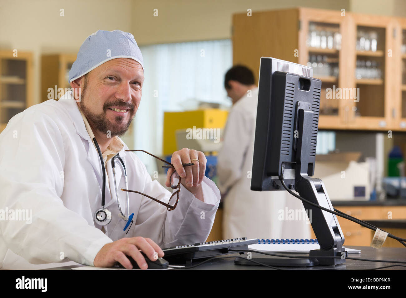 Lab technician working a  computer - Stock Image