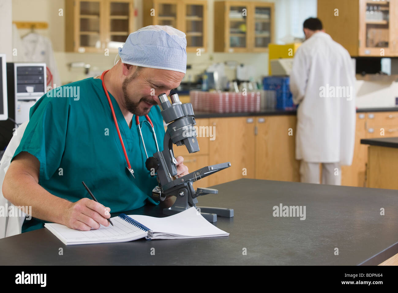 Scientist analyzing a sample through a microscope - Stock Image