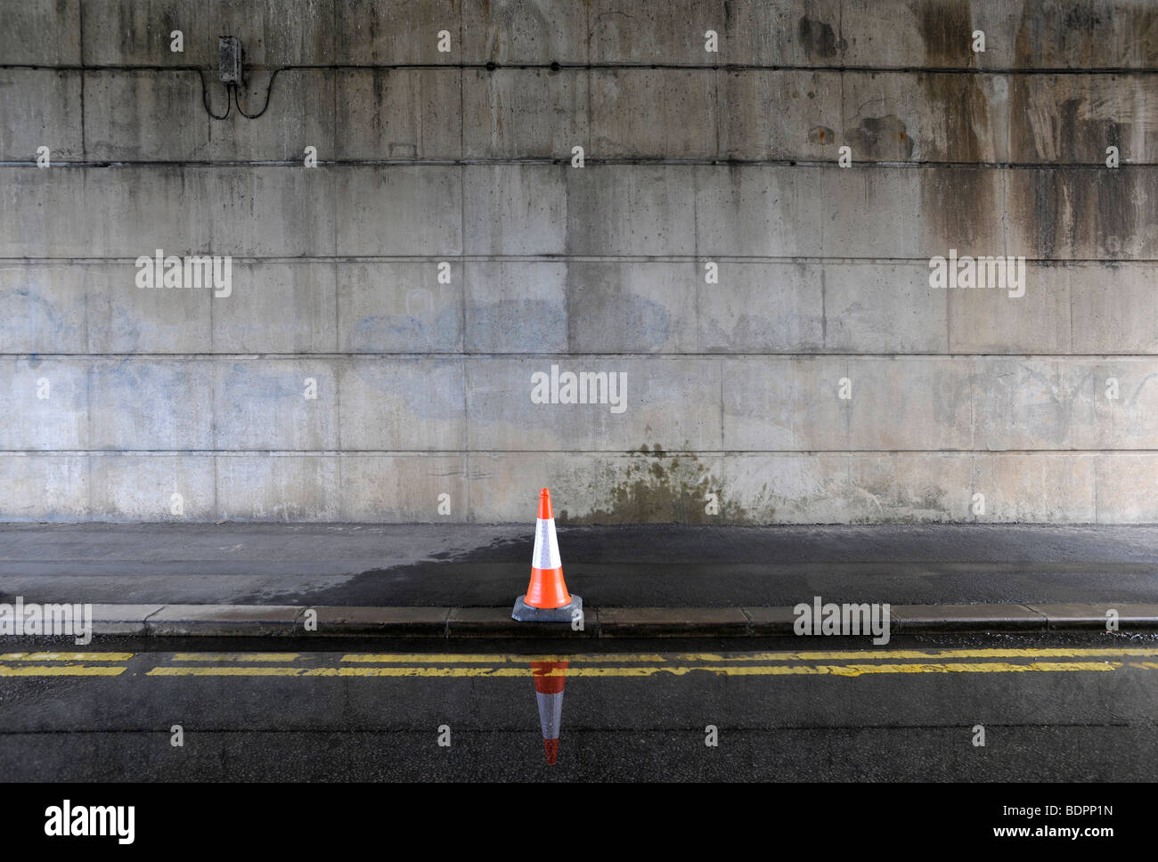 bollard on road near puddle of water - Stock Image