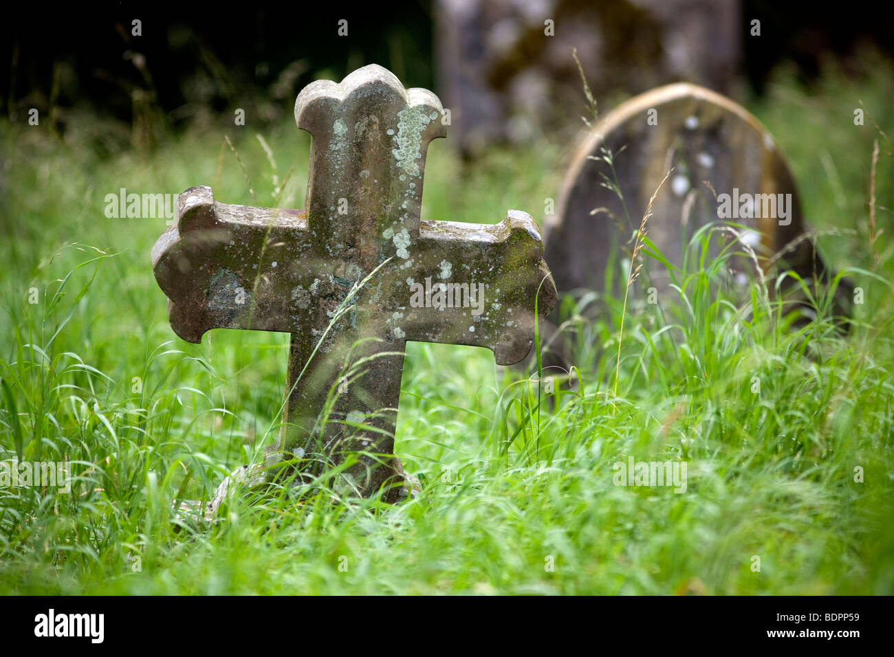 A grave stone in an over grown neglected church yard, Worcestershire, England, UK. - Stock Image