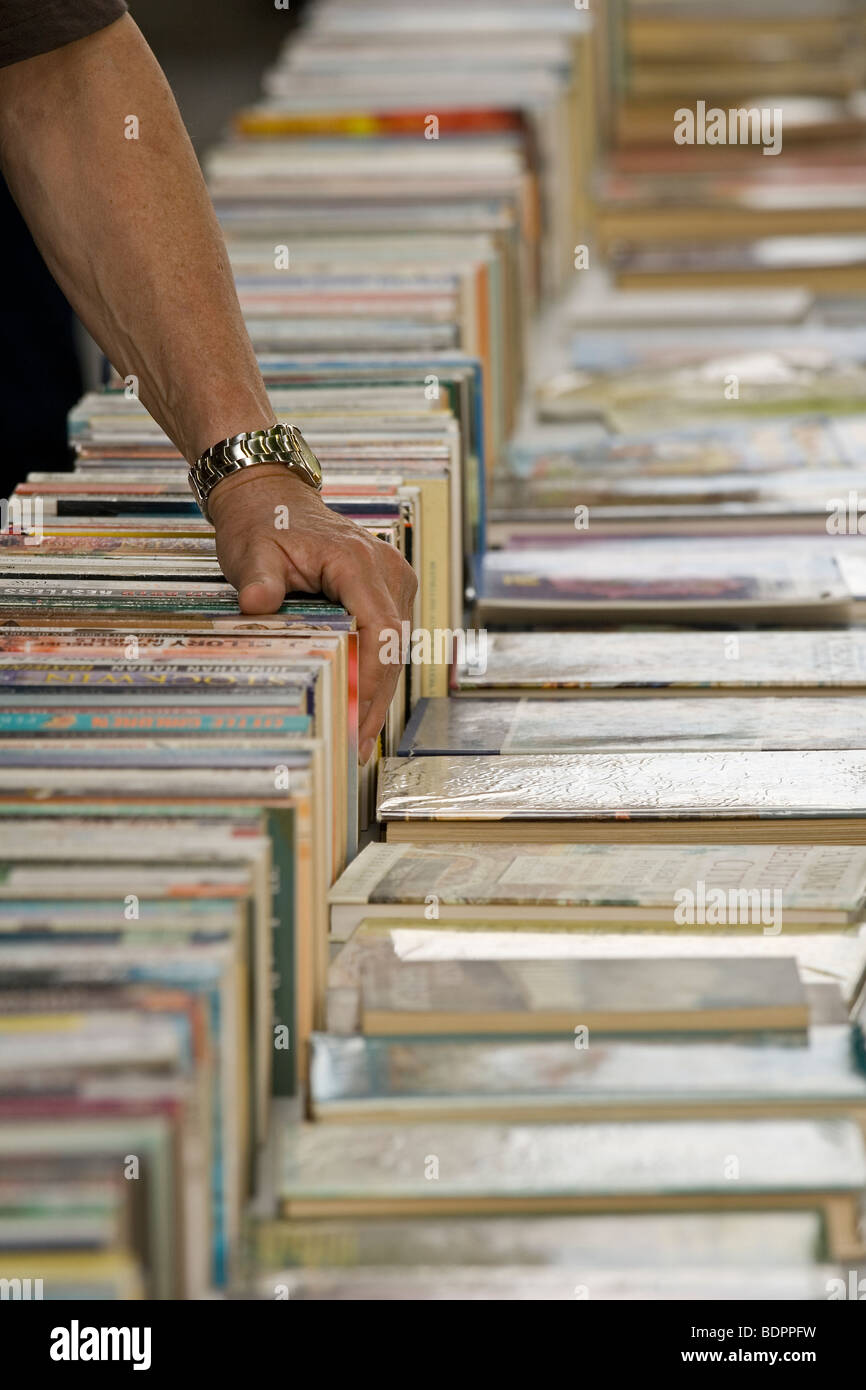 Person browsing at second hand book sellers on London's South Bank - Stock Image