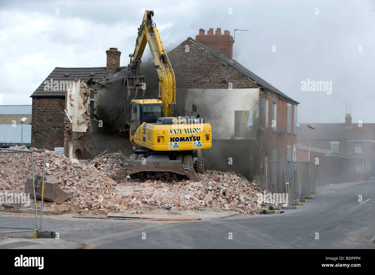 A bulldozer demolishes a terraced home in Yorkshire, UK. - Stock Image