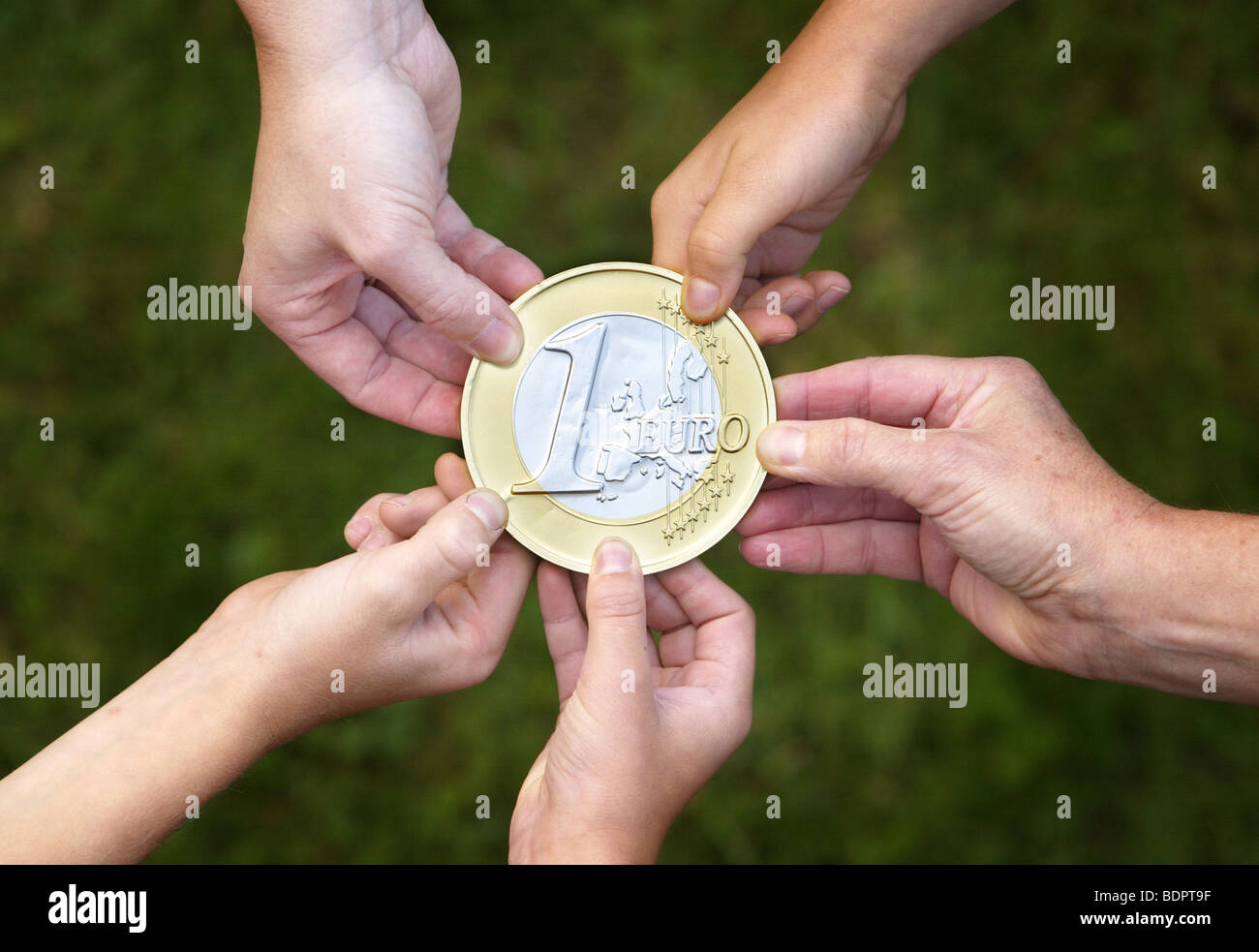 People holding a Euro-Coin Stock Photo